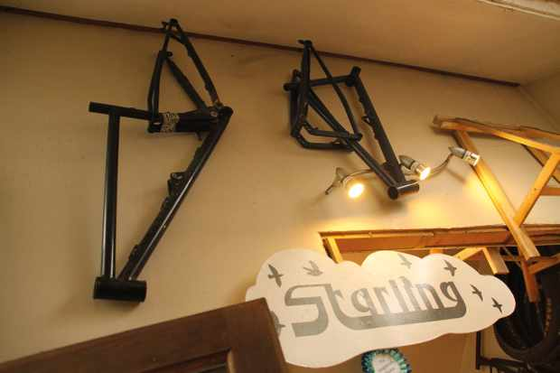 mountain bike frames hanging on the wall in Starling Cycles workshop