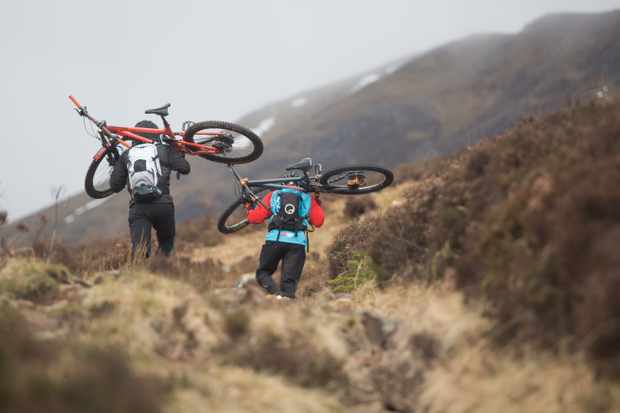 Neil Stewart and Brett Penfold carry their bikes up a steep climb on the Great Glen Way