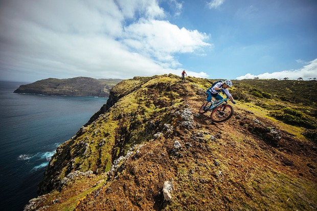 Two riders on a clifftop in the Azores overlooking the sea