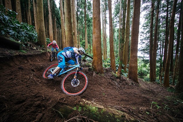 Two riders cornering in the forests of the Azores