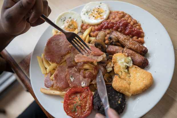 A customer eats the 'Super' full English breakfast at the 'Enough to Feed an Elephant' cafe in this arranged photograph in London, U.K., on Monday, July 10, 2017. British consumers could see the price of a fry-up -- a classic English breakfast with ingredients like bacon, sausages, orange juice, baked beans and mushrooms -- increase by almost 13 percent. Photographer: Simon Dawson/Bloomberg via Getty Images