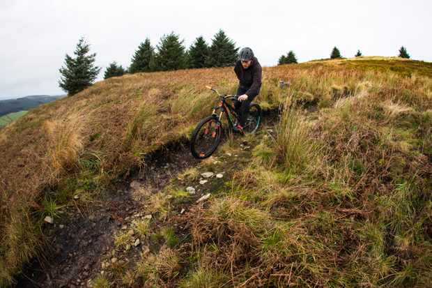 Tommy Wilkinson rides one-handed at Ae forest on a Scott Genius bike