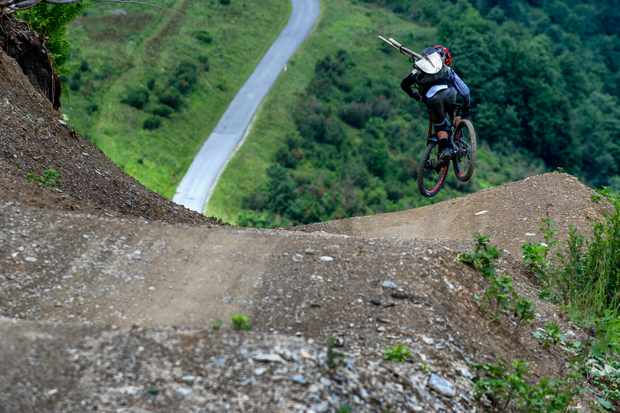 gatetan rey rides the vink line at bikepark chatel on a scott genius bike whilst carrying his tools on his back