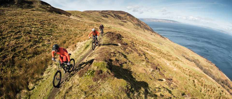Marc Beaumont and Ric McLaughlin riding along a coastal path on the Isle of Arran