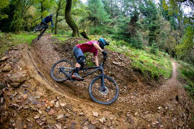 MBUK Staff members Alex Evans and Ed Thomsett ride a jump into a berm at BikePark Wales