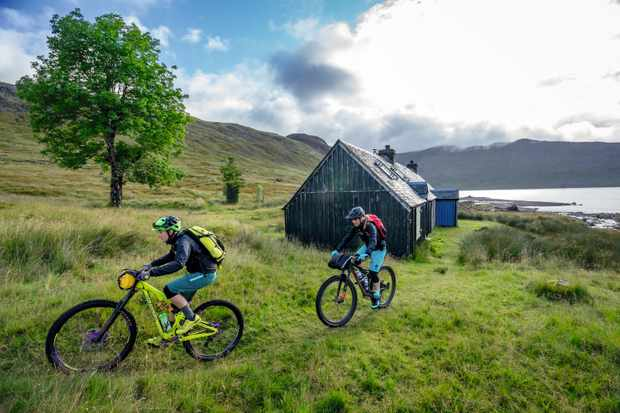 Rachael Walker and Hannah Barnes ride their bikes past a bothy in the Scottish Highlands