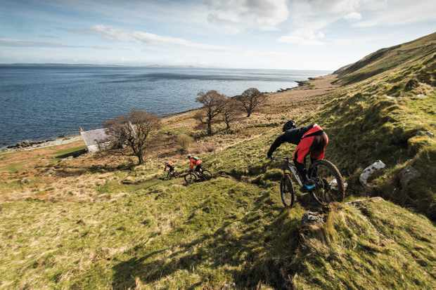 Riders head down to an abandoned cottage on the shoreline of Isle of Arran, Scotland