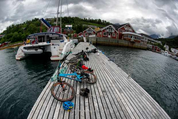 Bikes lying on the jetty next to a yacht in Norway
