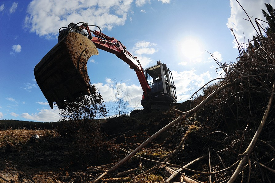 A big earth mover/digger in action, shaping mountain bike trails