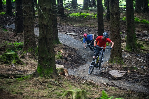 Two riders flowing down trail centre trails