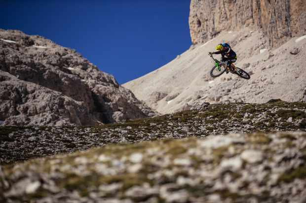 Cédric Gracia doing a bike jump in the Italian Dolomites
