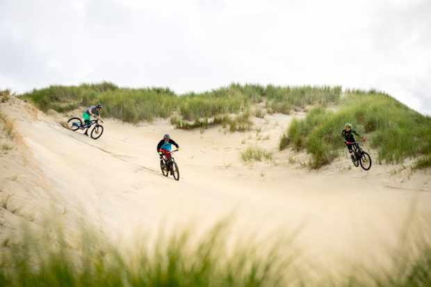 The Dudes of Hazard riding down a sand dune