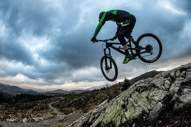 Downhill rider Adam Brayton jumping off rocks at Coed-y-Brenin in north Wales