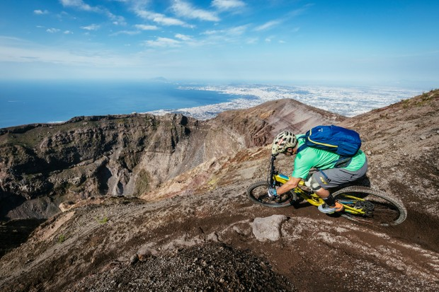 Don't look down! Hans rails around the lip of the giant crater on the still active volcano – Mount Vesuvius. The ancient Roman city of Pompeii is visible in the background, which was obliterated by an eruption in AD 79. Photo: Martin Bissig